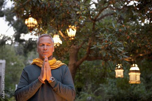 Older man praying in backyard