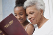 Older woman and granddaughter reading Bible together