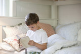 Boy reading Bible on bed