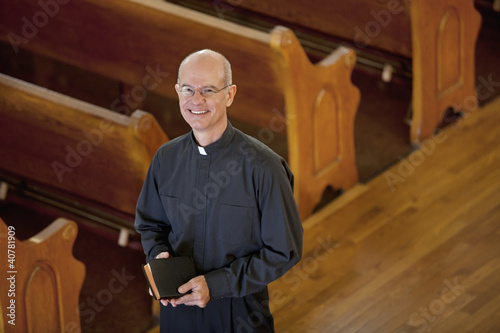 Smiling priest standing in church