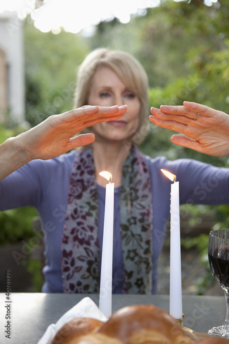 Woman holding hands over candles