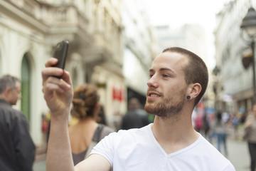 Urban photographer with mobila phone walking cross street and ph