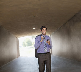 Businessman using cell phone in tunnel
