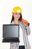 Female builder holding a laptop with a blank screen