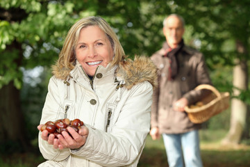 mature woman in woods with husband showing chestnuts