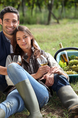 Couple with a glass of wine and basket of grapes