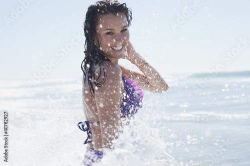 Woman in bikini splashing in water