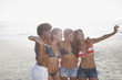 Women taking picture of themselves at beach