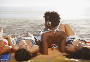 Women sunbathing together on beach