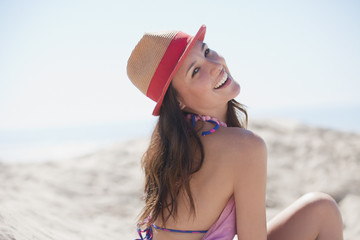 Smiling woman wearing sun hat on beach