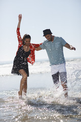 Couple playing in waves on beach