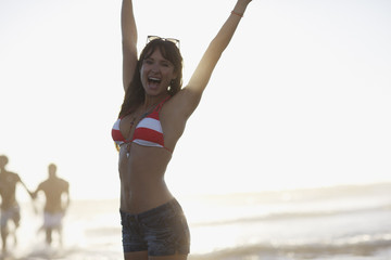 Smiling woman cheering on beach
