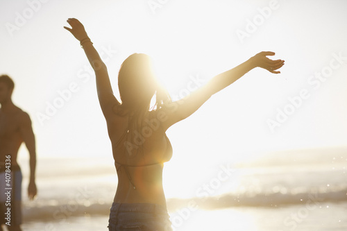 Woman in bikini cheering on beach