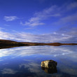 Clouds in blue sky reflected in still lake