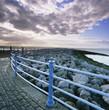 Railing along stone walkway near beach