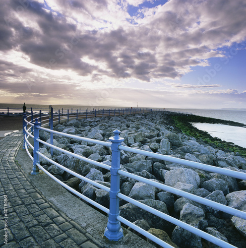 Railing along stone walkway near beach