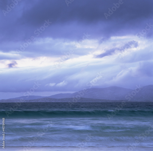 Clouds over rocky waters on beach