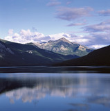 Rocky mountains and sky reflected in still lake