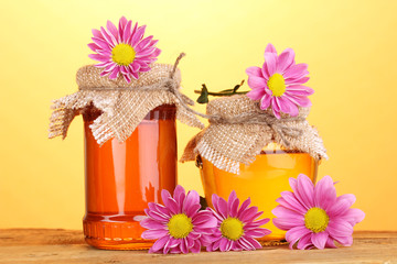 Sweet honey in jars on wooden table on yellow background