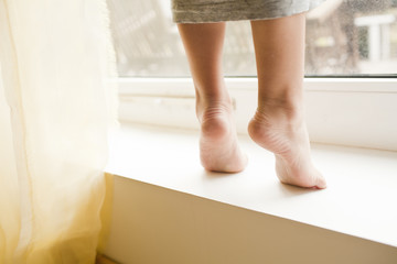 chidren's heel are on a window sill