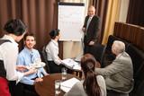 Business man at team meeting discuss flip-chart