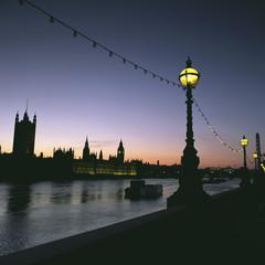 Streetlights along urban river at sunset