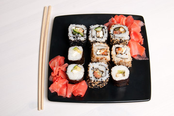 Sushi on a black plate on white table.