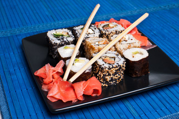 Sushi on a black plate on table.