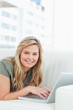 Close up, woman smiling and looking forward with her laptop in f