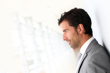 Businessman standing on white wall- profile view