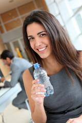 Portrait of office worker drinking water from bottle
