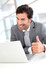 Portrait of cheerful businessman showng thumb up