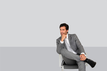 Businessman sitting on chair on grey background