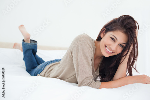 Woman lying on a bed, her hand in her hair smiling, with her leg