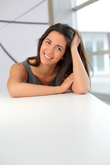 Beautiful woman sitting at desk with hand on hair