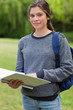 Young relaxed girl holding her notebook while carrying her backp