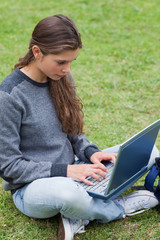 Serious young girl typing on her laptop while looking at the scr