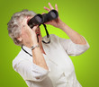 portrait of senior woman looking through a binoculars over green