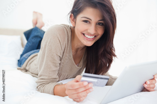 Woman looking straight ahead, with her credit card and tablet in