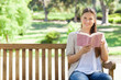 Woman sitting with a book on a park bench