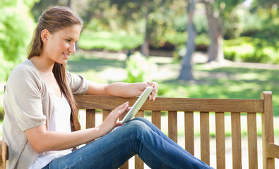 Side view of a woman using a tablet computer on a park bench