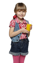 Little girl holding a glass with orange juice