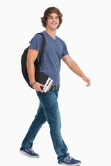 Male student with a backpack holding books while walking