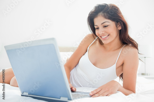 Woman relaxing across the bed with her laptop, enjoying what she