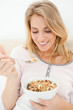 Close up, Woman looking at a spoon of cereal raised near to her