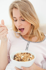 Close up, Woman about to eat a spoon of cereal, with a bowl in h