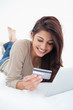 Close up, woman reading credit card infront of tablet