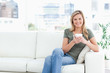 Woman sitting in the corneer of the couch, smiling with cup in h