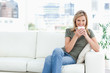 Woman smiling with a cup near her lips, sitting on the couch and