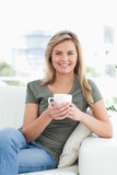 Woman holding a cup, smiling as she looks forward with crossed l